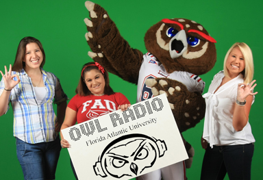 Students holding Owl Radio banner