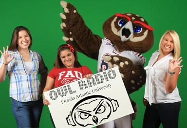 Students holding Owl Radio banner